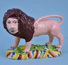 An unusual early 19th century Staffordshire pearlware model of a lion, modelled with a 'human' face, perhaps a political caricature and standing on a 'rainbow' coloured base.  Circa: 1825, England  Width: 18.00cm (7.09 inches)  Height: 13.50cm (5.31 inches)