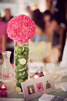 pink carnation sphere atop a vase filled with fresh limes- GREAT idea for preference centerpiece