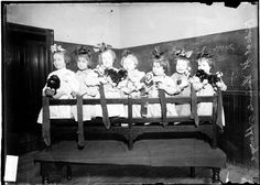 "December 23, 1909: Newspaper photo of seven Chicago orphan girls with their dolls and big bows in their hair. St. Vincent Orphan Asylum cared for children up to age 3. Perhaps this was an ""ad"" for prospective adoptive parents?"