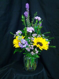 This arrangement is in a clear C999 and has 3 liatris, 2 sunflowers, 1 single bloom oriental lillys, 5 lavender moon carns, 3 lavender stock,  2 pink waxflower, 3 sala, 8 leather, and 2 myrtle.