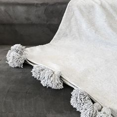 Plaid à pompons écru ou gris, composé de coton tissé et de laine, issu de l'artisanat marocain, confectionné à la main.  Peut servir de couverture, de descente de lit.  Dimensions : 200x200cm  Poids : 1,9kg
