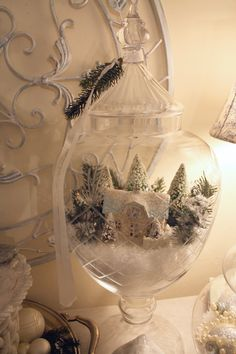 FIll an apothecary jar with faux snow, put a small cottage ornament on top and decorate it with trees and more snow.