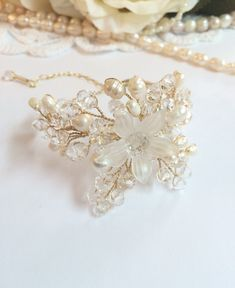 Absolutely gorgeous pearl wedding bracelet. Lovely piece of art for Your wedding day. The bracelet is handcrafted using goldplated artistic wire, acrylic flower beads, river pearls and glass crystals. Measures: about 3 inch diameter. The bracelet chain measures about 3 inches long.