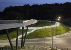 Concrete bridge by 2b Architectes links a station with a forest