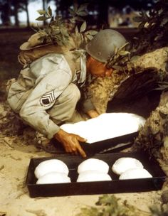 An American soldier makes bread using an improvised flue type oven dug into or constructed on the ground, during maneuvers in the United States, ca.1940s. (Photo by PhotoQuest/Getty Images)
