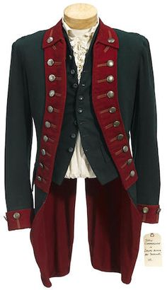 A John Carradine costume from Drums Along the Mohawk 20th Century Fox, 1939. Comprising a dark green (faded from blue) and dark red 18th century British-style military jacket with white metal buttons; a dark green wool vest; a cream cotton shirt with ruffled placket and cuffs and a black crepe neckband.