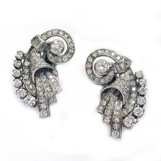 A pair of Art Deco diamond earrings, set throughout with brilliant-and baguette-cut diamonds, estimated to weigh a total of 2.90 carats for both earrings, circa 1925.