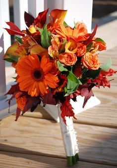 Orange gerbera, mango spray roses, mango calla lilies, orange alstromeria and fall leaves wrapped in white satin with pearls
