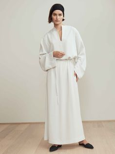 Mirabel is a luxurious long dress, featuring oversized, long sleeves and a deep V-cut at front. The dress features a tone-in-tone belt, to emphasize the waist. A relaxed, yet chic garment, perfectly worn to a vacation dinner. Style with a pair of mules for a more relaxed look or a pair of high heels for a more festive feeling. [...]Read More...