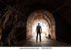 Young man stands in dark concrete tunnel and looks out in the glowing end by Eugene Sergeev, via Shutterstock