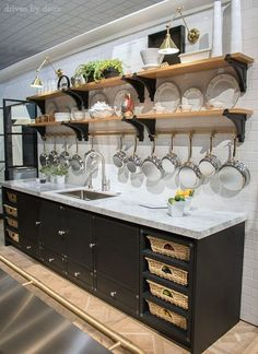 Fabulous La Cornue kitchen with open shelving, brass pot rack, swing-arm sconces, and cabinets with pull-out baskets