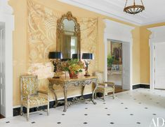 Trompe l'oeil–damask wall panels painted by Bob Christian Decorative Art grace the entry; the gilt-wood mirror from Florian Papp and the rococo console from Guy Regal are both 18th-century Italian, and the antique armchairs are covered in a Manuel Canovas linen.