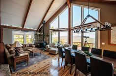 The post and beam frame of Moose Ridge Lodge makes the expansive wall of windows possible. #barnhomes #barnhouse #postandbeam #wallofwindows #loftceiling