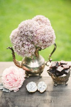 shabby chic flower arrangement of pink flowers and a silver tea pot.  great for outdoor picnic decoration