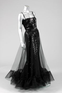 Yves Saint Laurent black sequined and tulle evening gown, Autumn-Winter, 1983, comprising black sequined camisole top edged in satin, the columnar sequined underskirt with satin waistband, tulle over-skirt with flounced hem