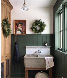 A farmhouse laundry room with deep green by oldfarmhouse. #huntergreen #laundryroom #farmhousestyle