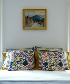 Rich blues, reds and yellows sit perfectly alongside more muted tones and greys. Pillows by Josef Frank.