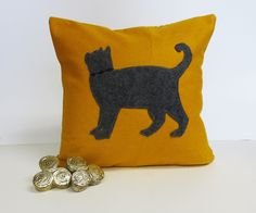 """Mustard Yellow Felt Pillow with Grey Cat Applique. Mustard Yellow Felt Pillow / Cover with Grey Felt Cat Silhouette ~*Construction*~ The front of the pillow is fabricated out of a mustard yellow felt. At the center there is a profile of a cat appliqued in grey eco friendly felt. The cat has a black embroidery collar. The back is black and ivory ticking stripe cotton with a exposed black zipper ~Dimensions & Other Info~ Cover accommodates a 12"""" x 12"""" (30.48 cm x 30.48 cm) pillow insert…"""