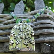"""This necklaces features a large (approx. 2"""") pendant with opening doors with vines decorating the front of it. I t has a flat inside and is perfect to adhere a picture to, It is paired with smoky gray, green and yellow glass chip beads. It is approx. 20"""" long before the pendant."""