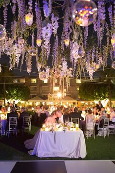 After the sun set, tables – including the newlyweds' sweetheart table – were aglow in candlelight, while amethyst uplighting colored the wisteria vines above the checkered dance floor. #receptiondecor Photography: Stephanie Fay Photography. Read More: http://www.insideweddings.com/weddings/sophisticated-garden-inspired-wedding-in-phoenix-arizona/659/