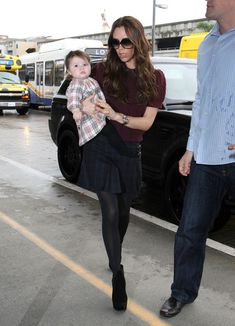 Victoria Beckham Ankle boots  Victoria accessorized her travel style with black tights and suede platform ankle boots.