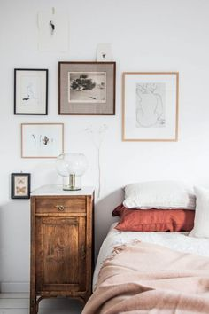 nightstand and hung photos / art by the bed