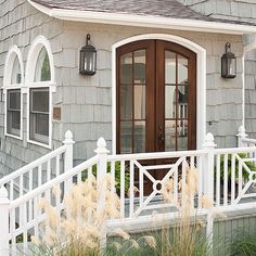 Curved doors add subtle style to this beachy facade. See more ideas for exterior doors: http://www.bhg.com/home-improvement/door/exterior/exterior-door-ideas/#page=13
