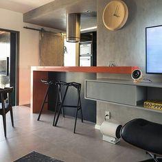 Cozinha integrada com bancada laranja, paredes e piso cinza/cimento queimado/ concreto, banqueta preta e gaveteiro laca.
