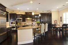 Gallery featuring images of 34 kitchens with dark wood floors. With the contrast between the different types of material in the cabinets and countertops, any kitchen can be transformed with a deep wooden color in the floors.