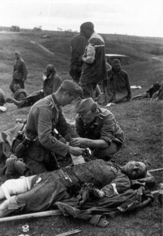 German medics offer assistance to a gravely wounded Red Army soldier. Both of the man's arms are smashed. His left arm, still unattended, is obviously in need of amputation. This photo was taken in July 1941, early on in the war with Russia. As the war progressed, assistance to Russian wounded lessened until it disappeared completely. By 1943, all Russian wounded were shot as a matter of routine.