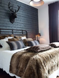 A rustic male bedroom makes a class act design statement in a loft apartment, using split logs for one wall and combining a deer head with a faux fur throw over the bed clothes. Kind of a sexy male with a come hither look. :-)