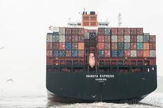 Containerschiff im Hafen von Hamburg bei starkem Nebel. Hinten sieht man das Rettungsboot, das aussieht wie ein U-Boot.