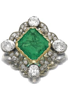 Emerald and diamond brooch, second half of 19th century and later. Set with cushion-shaped, oval and circular-cut diamonds, later set to the centre with a step-cut emerald, later brooch fitting.