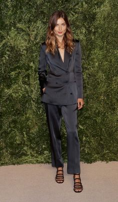 Andrea Diaconu wears a silk black suit with black strappy sandals.