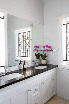 Beautiful ensuite in white 2pac featuring charcoal Caesarstone bench-tops, chrome hardware and under-mount sinks.