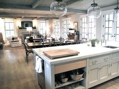 Jane Green Figless Manor - Beautiful open kitchen design with rustic coffered ceiling, wall of French doors, creamy light gray kitchen cabinets with marble countertops, sink in kitchen island, stacked dishwashers, glass pendants, rectangular dining table - Picmia