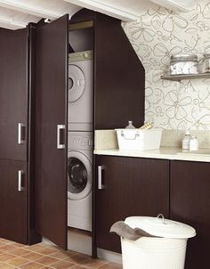 Rentabiliza bien el espacio. Para lograrlo, una buena opción es colocar en columna la lavadora y la secadora; así aprovechas el espacio vertical. Aquí, además se ocultaron tras un mueble laminado en wengué