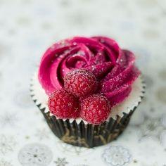 White cupcake with raspberry frosting & fresh raspberry decor