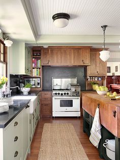 An apron-front sink, antiqued-brass bin pulls, honed soapstone, and a mix of painted and wood cabinets create a homey, rustic-modern mix.
