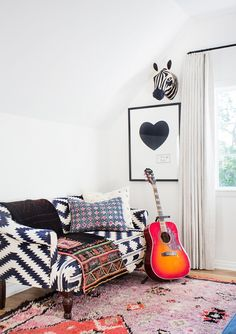 White bedroom with black and white sofa and guitar in corner