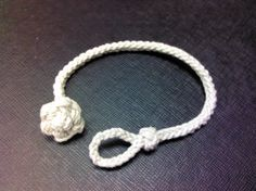 """This is a Chesapeake Waterman's Bracelet I did up in #18 natural cotton. It is made with 3, 40"""" lengths of string, middle, with a 3 strand braid catch loop, into a 4 strand foot rope knot (2 from each side of the loop, and the remaining 2 in the core), then a 6 strand half round or reefing braid with a star knot catch. Originally from Frayed Knot Arts: http://www.frayedknotarts.com/tutorials/chesapeake/chesa.html"""