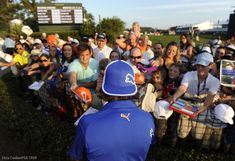 """""""Rickie and his fans - There are a few players throughout the history of the game who have been real fashion icons and influenced fans to dress just like them. Rickie Fowler with his colorful clothes and flat-brimmed hat has become one of the most duplicated looks by fans of all ages. His fans always line up for autographs after his round, and he usually spends some time making their day."""" -- Chris Condon, PGA TOUR Photographer"""