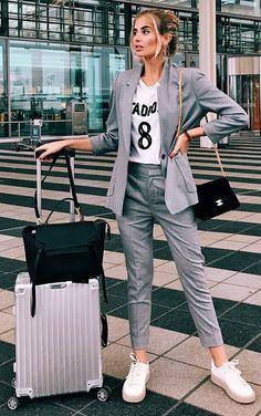 Athleisure: como inserir peças esportivas em seu look. Terno femininino, blazer cinza, t-shirt branca estampada, calça de alfaiataria cinza, tênis branco