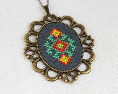 If you love ethnic pieces and unique jewelry, youll adore this stylish Ethnic hand-embroidered necklace. With a special vintage look, it becomes a wonderful addition to your everyday outfit. Wearing this necklace, youll receive a whole raft of compliments!  The necklace is made on hand dyed linen fabric with cotton embroidery floss.  • Pendant is 5.2 cm x 6 cm (2 x 2 2/8) • Embroidered piece is 3 cm x 4 cm (1 2/8 x 1 5/8) • Default length of chain is 55 cm / 22. • All findings are bronze…