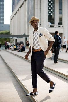Mens street style fashion: white cream linen jacket, navy pants, tan fedora hat, white navy striped tshirt, tan leather belt, navy and white soludos loafers