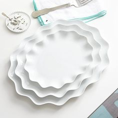 The delicate and graceful Mallorca dinnerware collection is dedicated to fluid forms—wavy, sinuous and curled—in an absence of color, using only white to explore light and shadow. Designed by Paola Navone to be mixed, juxtaposed and overlaid for inspired table settings, white porcelain platters scallop at the rim like flower petals or seashells.