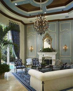 Opulent blue living room  with decorative wall paneling, stunning ceiling design, carved wood Italian mirror above the white marble fireplace mantel, and pair of Louis XV style carved wall sconces