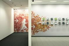 Boldly colored and patterned wall graphics energize the company fitness center. A grid of ball caps celebrates TD Ameritrade's sport and community events.