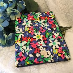 Kate Spade Floral iPad Case Very fun and colorful Kate Spade iPad case.  Vinyl coated cloth with white, blues, greens, reds and yellow floral pattern.  Front has silver Kate spade logo spade.  Not cuts or tears or stains on exterior, but there is a light indentation from something resting on it.  Interior is a rubbery cloth with rubber framing where iPad sits.  Interior does show some wear, but not cuts or tears. kate spade Accessories Tablet Cases