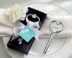 "This elegant ""Key to My Heart"" Victorian Style Bottle Opener makes a unique and elegant favor. Made of high quality chrome, the silver opener is shaped like an antique key. Kate Aspen's chrome favors are solid chrome-with a notable weight and lasting quality.  Each opener is presented in a black velvet lined gift box with a clear top. The favor is complete with a sheer organza ribbon and a designer hang tag that reads ""Key to My Heart."" The key opener measures 4"" x 1.5"" and each gift box…"